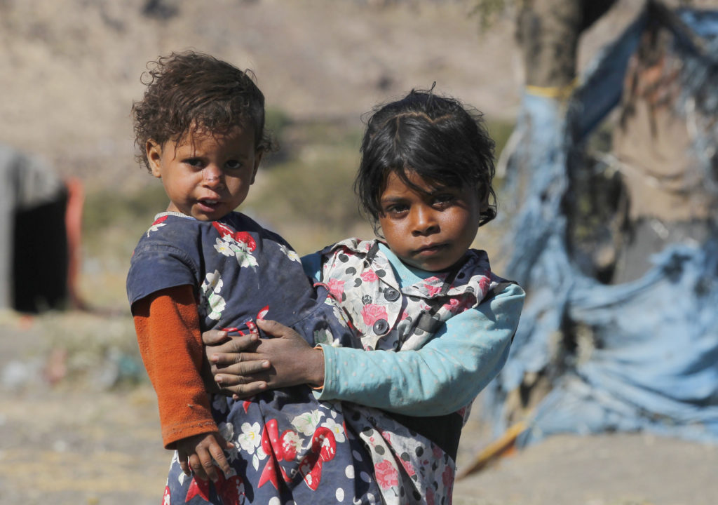 A girl holds her sister near a makeshift shelter at a camp for displaced people on the outskirts of Sana'a, Yemen. (CNS photo/Yahya Arhab EPA)